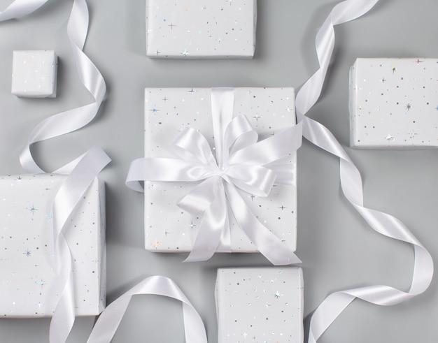 Verpakte grijze geschenkdozen met wit lint op grijze bovenaanzicht