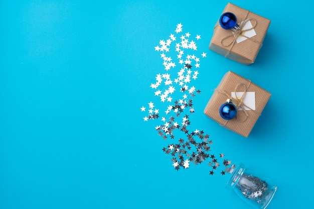 Verpakte kerstcadeaus met confetti op blauwe achtergrond bovenaanzicht