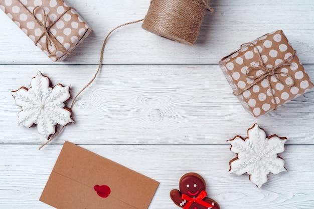 Verpakte kerstcadeaus op wit houten bord, bovenaanzicht, kopie ruimte
