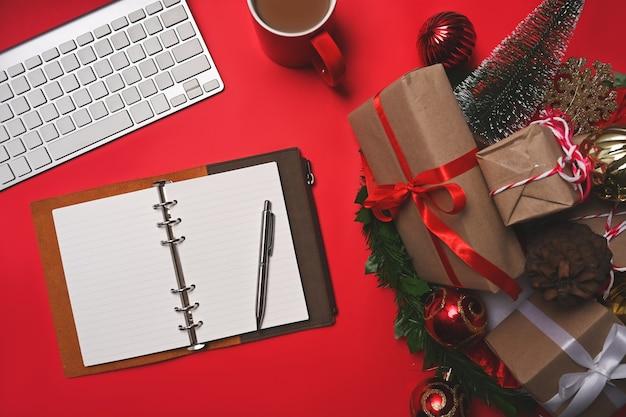 Verpakte kerstcadeautjes, dennenappel en kopje koffie op rode achtergrond.