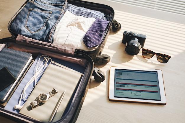 Verpakte koffer op bureau, tablet met eticket op scherm, camera en zonnebril