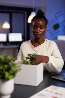 Verplaatste afro-amerikaanse zakenvrouw die objecten in een kartonnen doos stopt