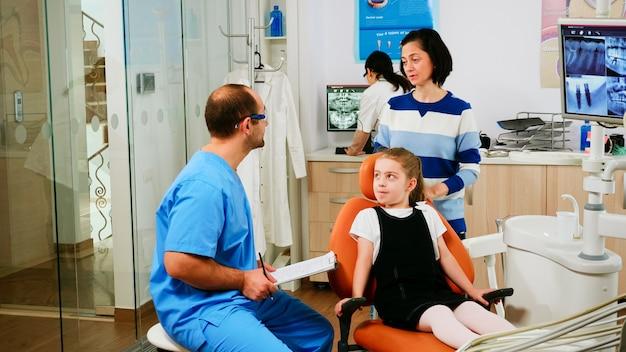 Verpleegkundige die aantekeningen maakt op het klembord over gebitsproblemen bij kleine meisjes die op orthodontist wachten. assistent die medische procedure uitlegt aan haar moeder die in de buurt van stomatologische stoel staat.