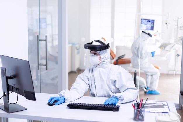 Verpleegkundige die computer gebruikt tijdens covid 19 draagt pbm-pak als veiligheidsmaatregel. medicijnteam dat als veiligheidsmaatregel beschermingsuitrusting draagt tegen een pandemie van het coronavirus bij de tandheelkundige receptie.