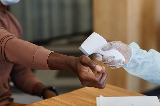 Verpleegkundige die de temperatuur van de patiënt meet