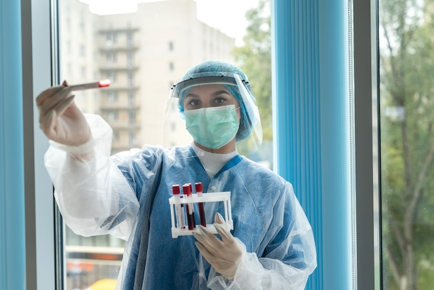 Verpleegkundige die een uniform met gezichtsschild draagt met een positief bloedtestresultaat voor covid-19. concept van covid-19 quarantaine.