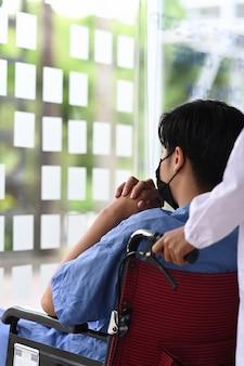 Verpleegkundige die mannelijke patiënt op rolstoel bijstaan.