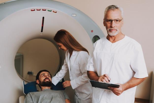 Verpleegkundige die patiënt voorbereiden op ct-scan in kliniek