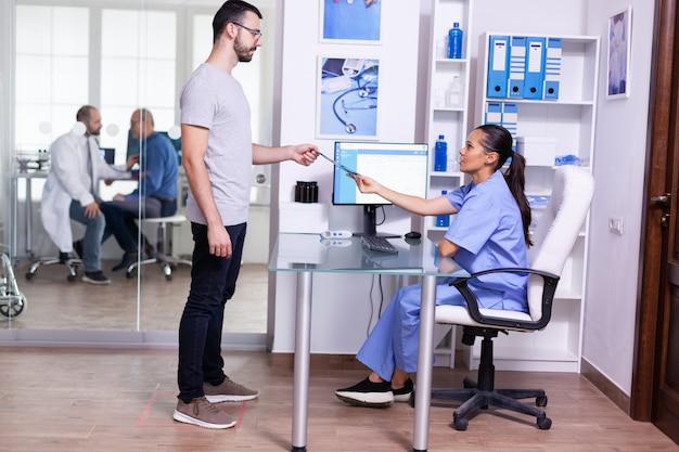 Verpleegkundige die patiëntröntgenfoto geeft bij de receptie van het ziekenhuis met een blauw uniform
