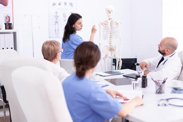 Verpleegkundige die presentatie geeft voor artsenteam over menselijke anatomie die skelet gebruiken. kliniek deskundige therapeut in gesprek met collega's over ziekte, medische professional.