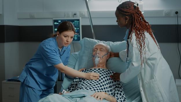 Verpleegkundige die zieke patiënt raadpleegt in ziekenhuisafdeling bij kliniek