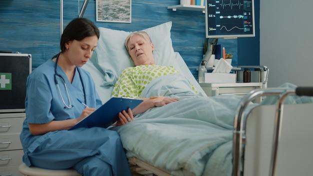 Verpleegkundige doet gezondheidszorgcontrole met oude vrouw in bed