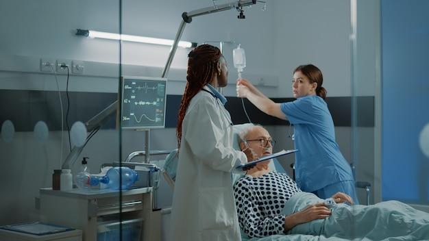 Verpleegkundige en afro-amerikaanse arts behandelen zieke patiënt in ziekenhuisafdeling met moderne medische apparatuur...