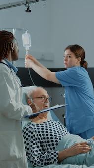 Verpleegkundige en afro-amerikaanse arts behandelen zieke patiënt