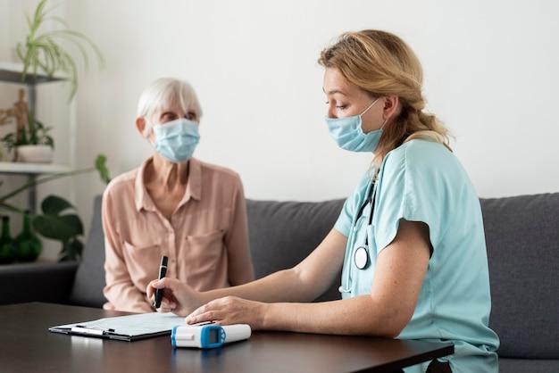 Verpleegkundige en senior vrouw tijdens een controle in het verpleeghuis