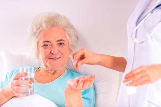 Verpleegkundige geeft pillen aan oudere oma in bed.