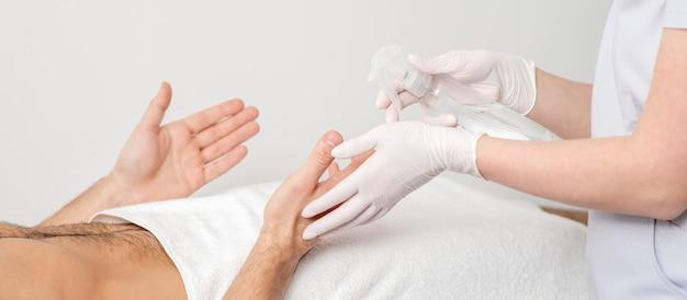 Verpleegkundige hand sanitizing handen van mannelijke patiënt in het ziekenhuis. coronavirus bescherming concept.