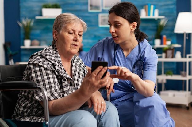 Verpleegkundige helpt gepensioneerde senior vrouw in rolstoel om smartphone te gebruiken tijdens sociale dienst