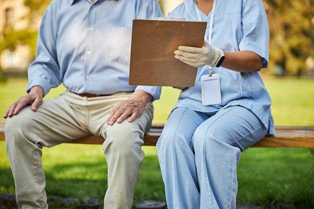 Verpleegkundige houdt dossiermap vast en zit naast haar patiënt