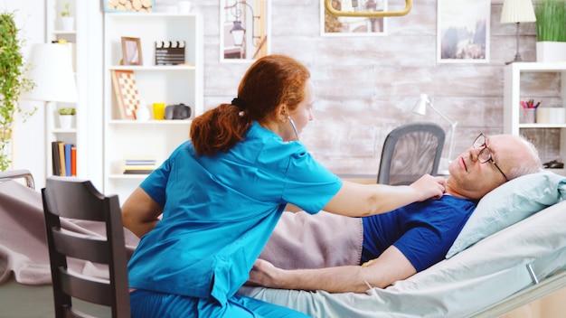 Verpleegkundige in bejaardentehuis luisteren naar oude zieke man hart kraal. de gepensioneerde ligt in een ziekenhuisbed