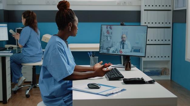 Verpleegkundige in gesprek met arts via videogesprekverbinding in kast