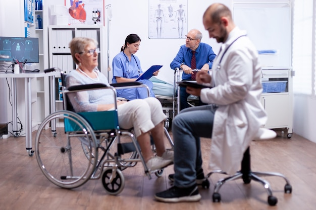 Verpleegkundige in gesprek met gehandicapte man in ziekenhuiskamer tijdens consult
