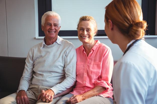 Verpleegkundige in gesprek met senior paar