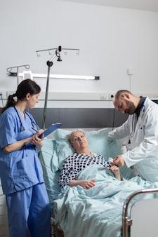 Verpleegkundige maakt aantekeningen op klembord tijdens consultatie van senior vrouw, terwijl arts gegevens leest van oxymeter over pols, bloedpuls en zuurstofverzadiging aangesloten op zieke patiënt aangesloten op f