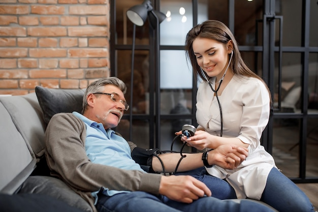 Verpleegkundige meet de bloeddruk van een oude man. een oudere patiënt met hoge bloeddruk thuis bed. mensen en het voorkomen van hart-en vaatziekten.