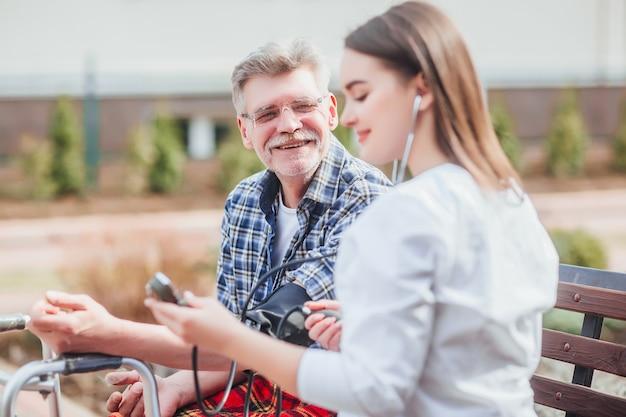 Verpleegkundige meet een oude man in de tuin van de kliniek. in de buurt van verpleeghuis