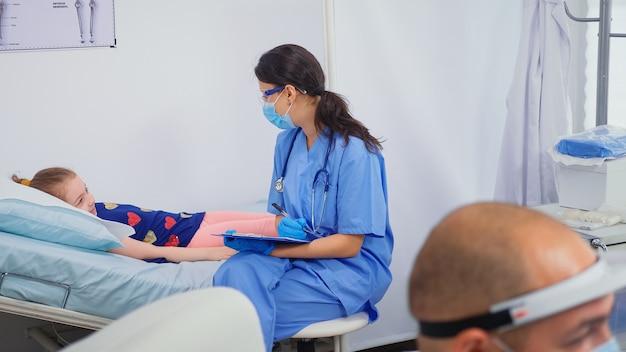 Verpleegkundige met beschermingsmasker in gesprek met kind dat in bed ligt. arts-specialist in de geneeskunde die gezondheidszorg verleent behandeling consultatie onderzoek in ziekenhuiskast tijdens covid-19