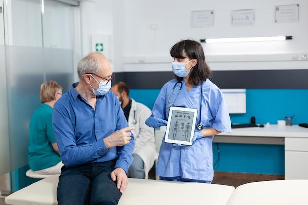 Verpleegkundige met digitale tablet met menselijk skelet op afbeelding