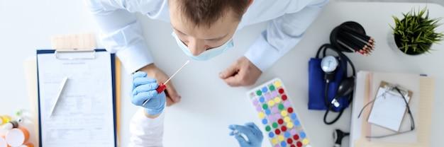 Verpleegkundige met medisch masker dat uitstrijkje neemt van de neus van de patiënt bovenaanzicht vaderschap dna-testconcept