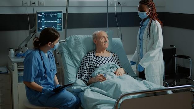 Verpleegkundige met tablet die zieke patiënt in ziekenhuisbed adviseert