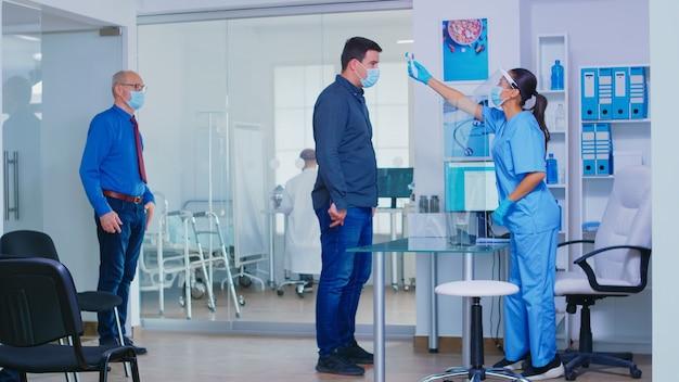 Verpleegkundige met vizier tegen covid19 in wachtruimte van het ziekenhuis die de temperatuur van de patiënt meet met behulp van een infraroodthermometer. assistent met gezichtsmasker die gehandicapte senior vrouw in rolstoel duwt.