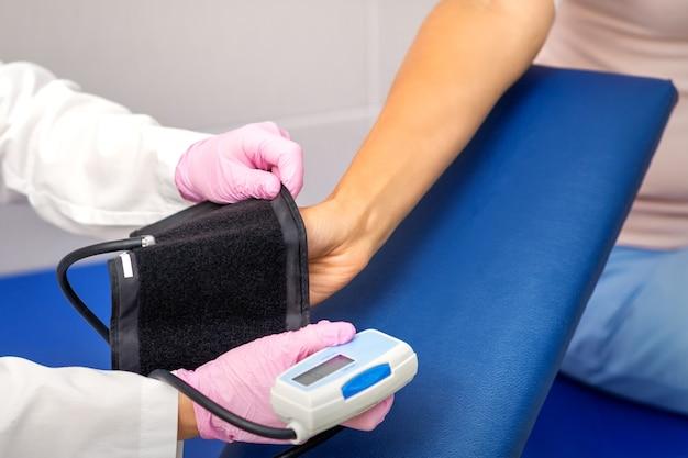 Verpleegkundige of vrouwelijke arts zet tonometer op de arm van de jonge vrouw in het ziekenhuis