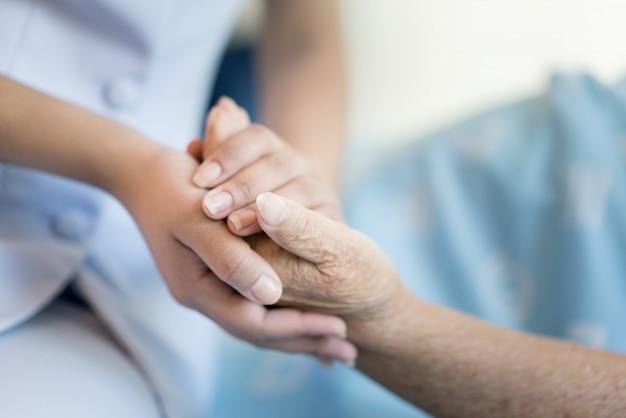 Verpleegkundige zittend op een ziekenhuisbed naast een oudere vrouw die handen helpt