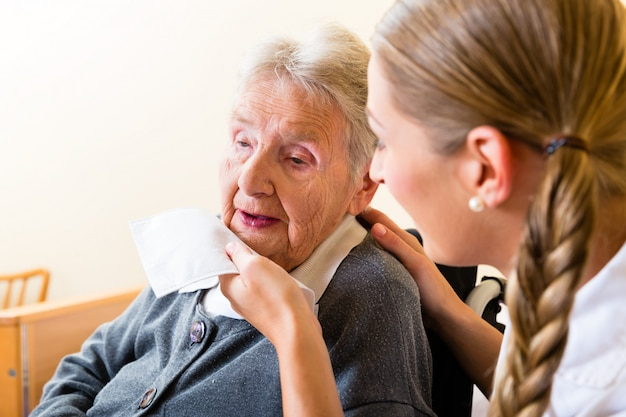 Verpleegster afvegende mond van hogere vrouw in verpleeghuis