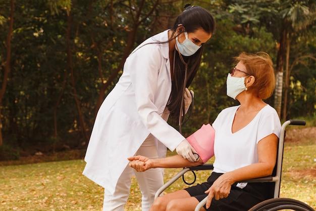 Verpleegster arts die de druk van oudere vrouw meet