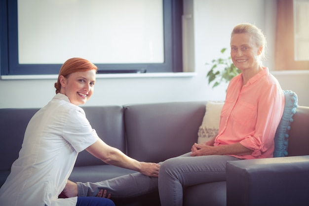 Verpleegster die beenmassage geeft aan vrouw