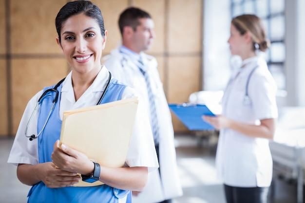Verpleegster die bij de camera in de ziekenhuisafdeling glimlacht