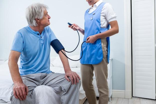 Verpleegster die bloeddruk van de hogere mens thuis controleert