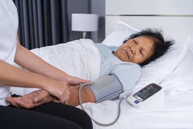 Verpleegster die bloeddruk van een hogere vrouw controleren op bed