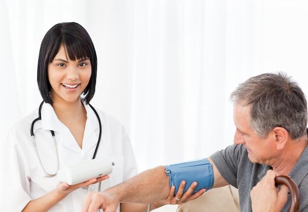 Verpleegster die bloeddruk van haar patiënt neemt