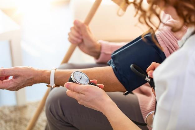 Verpleegster die bloeddruk van hogere vrouw thuis meet.