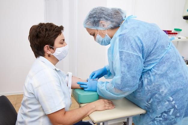Verpleegster die bloedonderzoek uit ader doet. covid-testconcept
