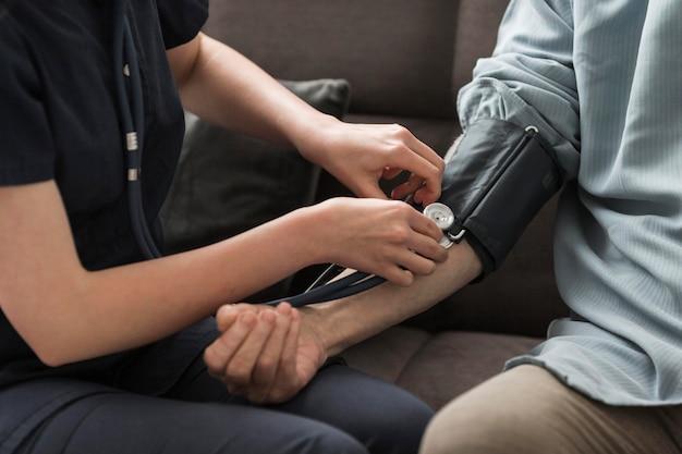 Verpleegster die de bloeddruk van de oude man in een verpleeghuis controleert