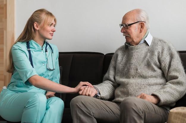 Verpleegster die de hand van de oude man in een verpleeghuis houdt