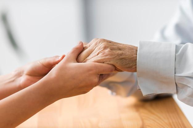 Verpleegster die de handen van de hogere man voor comfort houdt