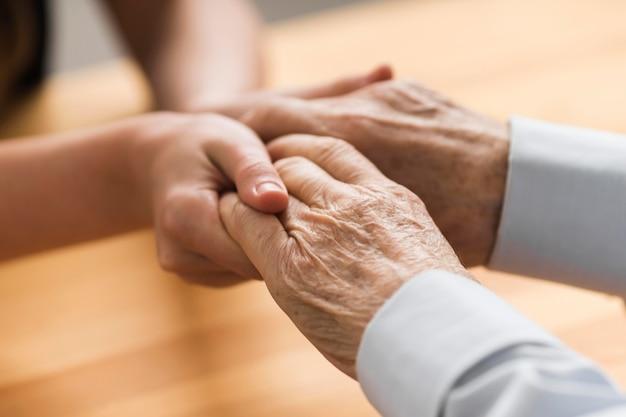Verpleegster die de handen van de hogere man voor empathie houdt